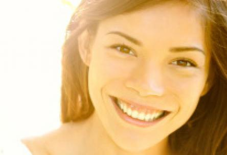 Photo: Smiling woman with bright sun behind her