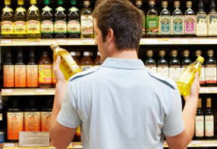 Photo: Man looking at two bottles of olive oil in supermarket aisle