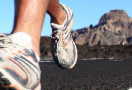 Photo: Close-up of running feet with mountain in background