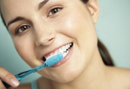 Photo: Woman brushing teeth with a wide smile