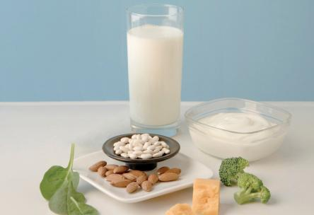 Photo: A setting of calcium-rich foods: glass of milk, yogurt, almonds, broccoli, cheese.