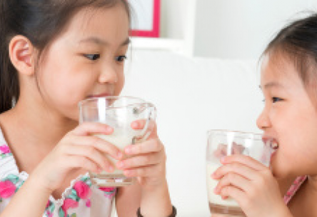 Photo: Two young girls drinking glasses of milk