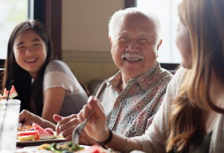 Photo: Elderly man smiling at dinner table with two granddaughters.