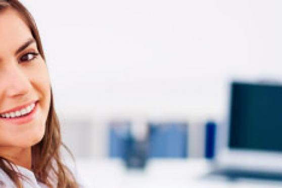 Photo: Happy young woman in bright office setting