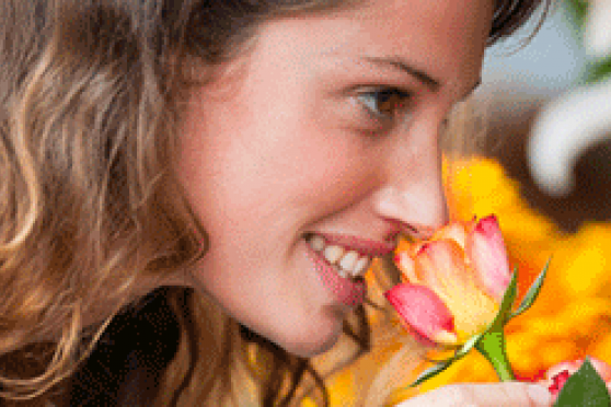 Photo: Young woman smelling a fresh flower