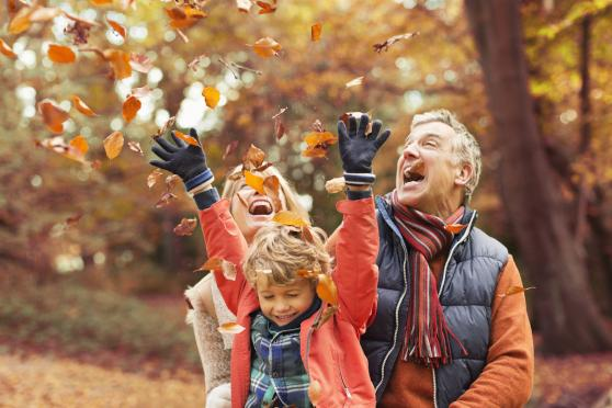 family having fun with fall leaves