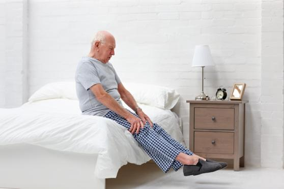 Photo: Senior man stretching in bed