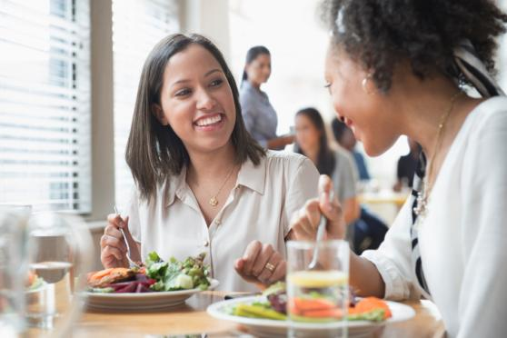 Women eating healthy and laughing