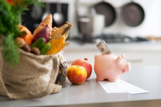 Photo: Piggy bank on kitchen counter next to a bag filled with fresh produce