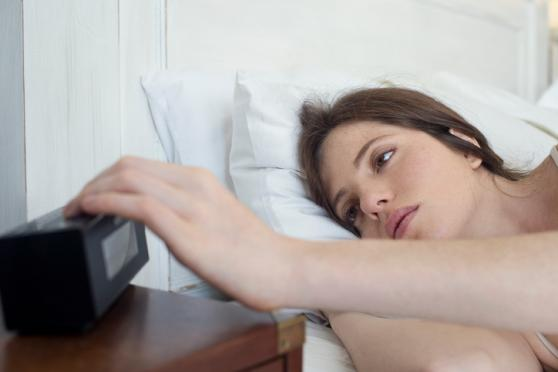 Restless Woman looking at alarm clock