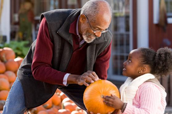 Grandfather and granddaughter at a pumpkin patch