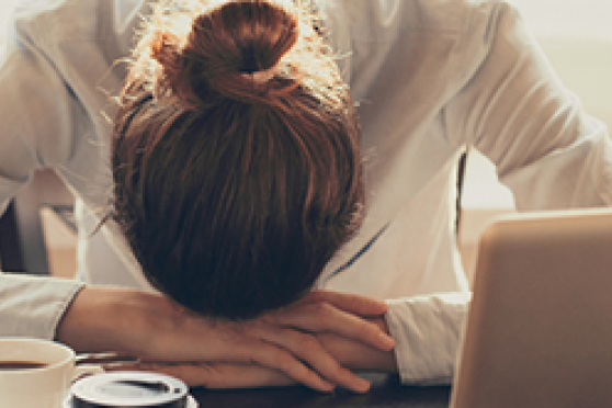 Photo: Stressed out woman resting her head on desk