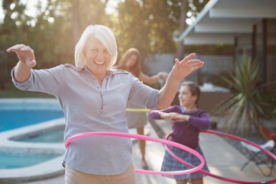 Photo: Mature woman laughing and playing with a hula hoop.