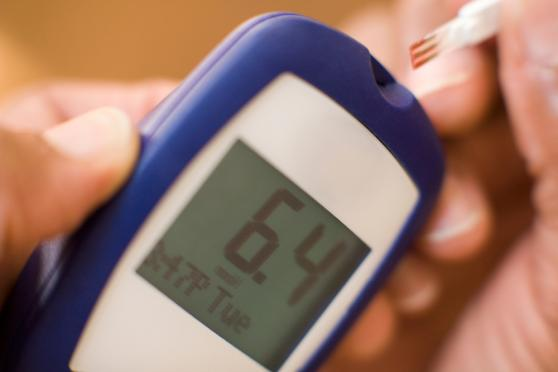 Photo: Close-up of person using glucose tester.