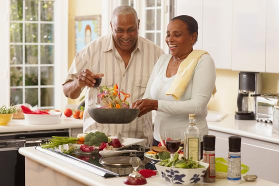 Photo: Man and woman cooking a healthy meal together.