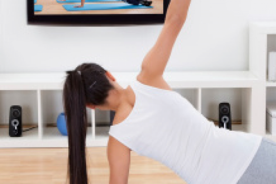 Photo: Woman doing an at-home workout in front of television